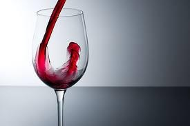 glass with red wine being poured